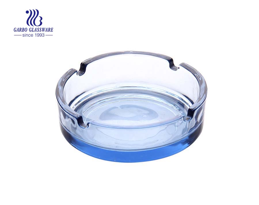 Clear glass ashtray with foundation and grooves for living room